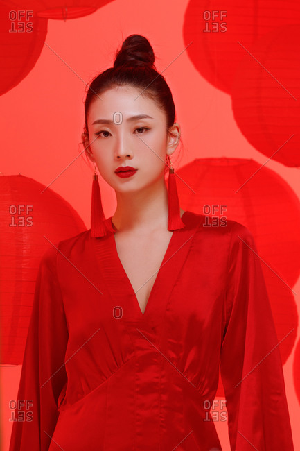 A female Asian model dressed in red standing against background with red lanterns
