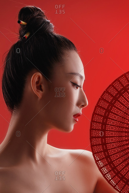 Beautiful female Chinese model posing with a fan against a red background
