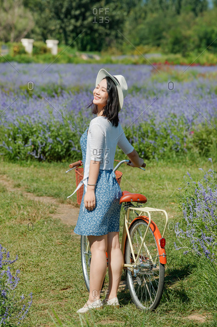 A young woman standing beside a cruiser bicycle in a field of lavender on a sunny day