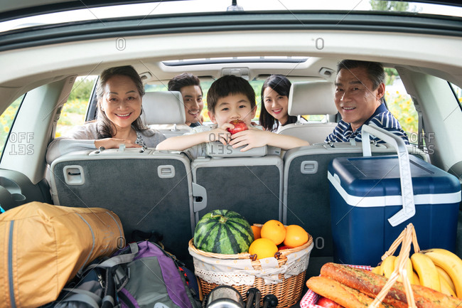 Family turning back to look at camera while snacking in car on road trip