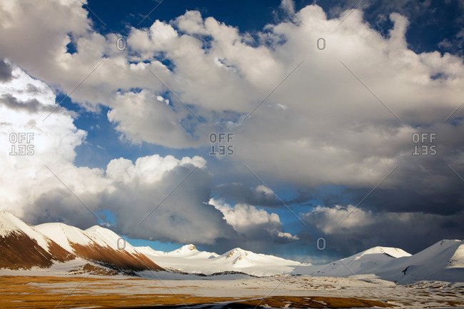 Fluffy clouds above snow-covered hills in Tanggula Mountains in the Tibet Autonomous Region