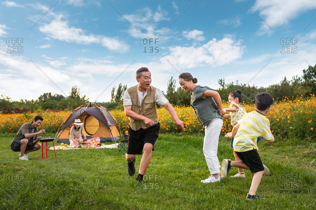 Multi-generational family having fun in a field on camping trip