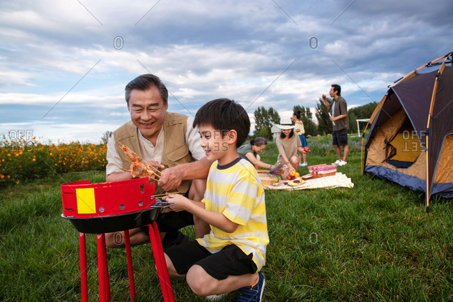 Happy family barbecuing in a field on camping trip