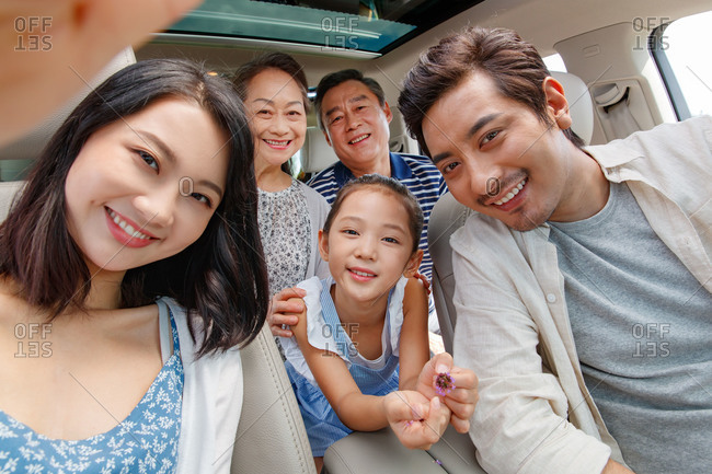 Selfie portrait of a multi-generational family sitting together in a car