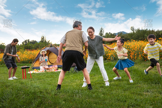Happy family playing together in a field while camping and dad barbecues