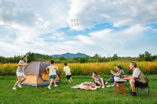 Mother chasing children around tent while husband and senior parents enjoy picnic on family outing