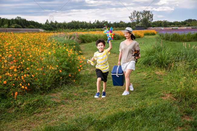A young mother walking with her son in a field with flowers