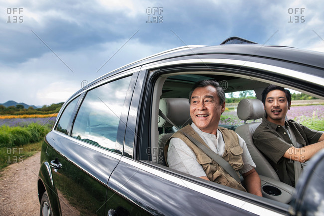 Father and adult son riding together in a car on a cloudy day