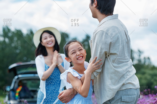 Happy little girl running to hug her father as mother watches from the background