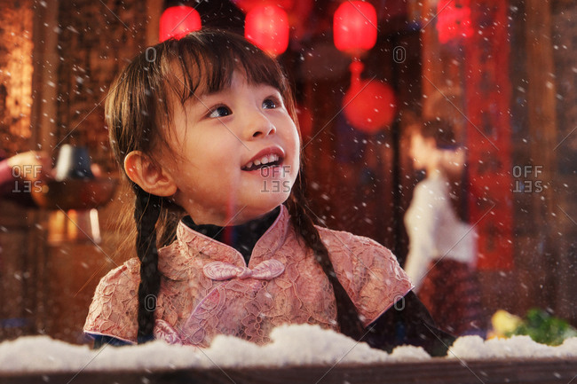 Lovely little Asian girl looking out a window as it snows