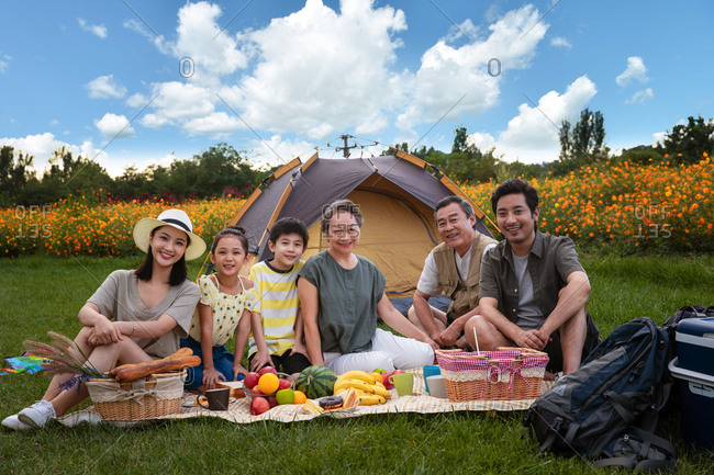 Portrait of a happy family having a picnic in a field during a camping trip