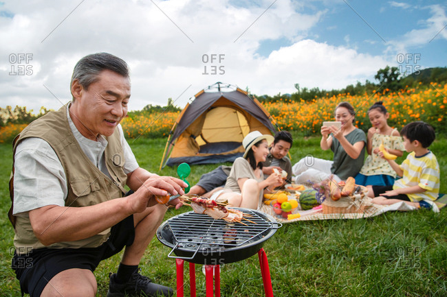 Senior Asian man preparing food on a barbeque with family on picnic blanket in background
