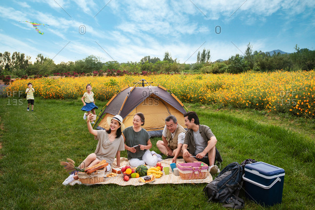 Woman taking selfie of her family having a picnic on a camping trip in the countryside