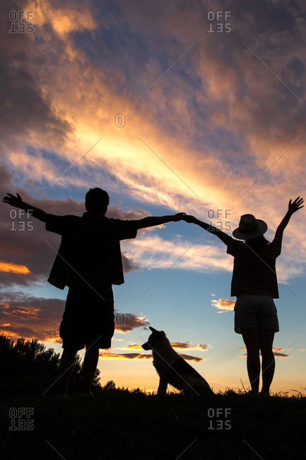 Silhouette of happy couple standing hand in hand with a dog in the sunset