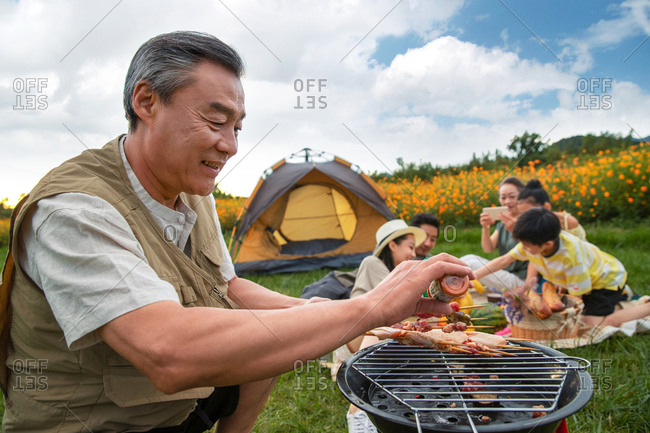 Senior man preparing food on the barbecue with his family in the background