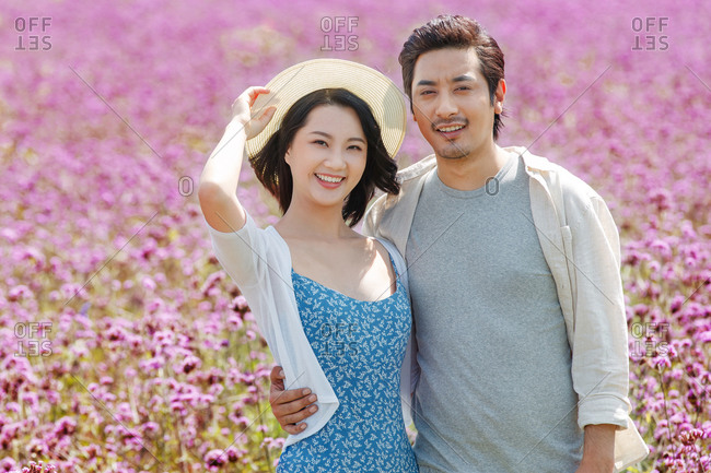 Happy young couple stood in the flower sea