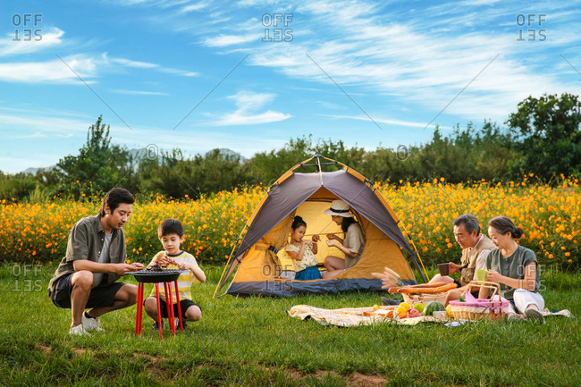Multi-generational family in a field camping, having a picnic and barbequing