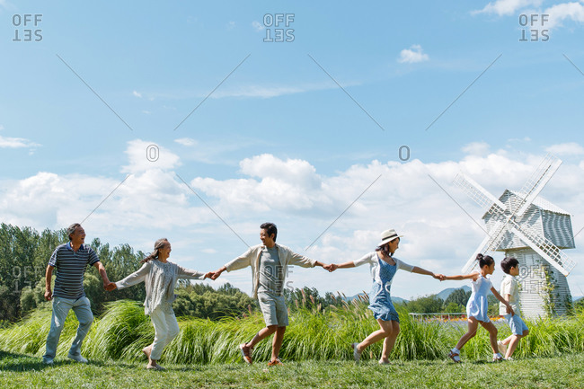 Beautiful Asian family walking hand in hand in a field in front of a windmill