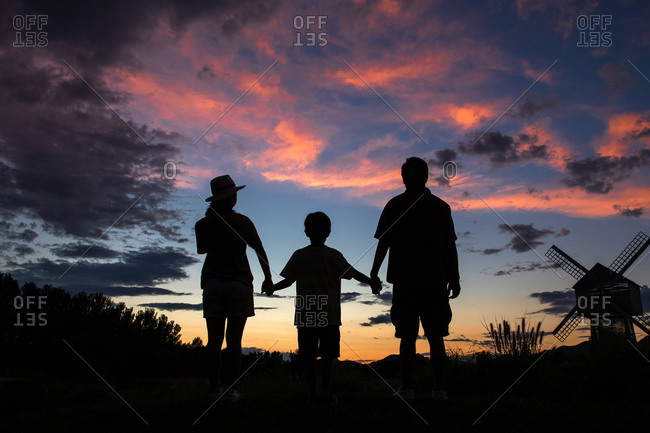 Silhouette of parents and child holding hands in front of the sunset sky