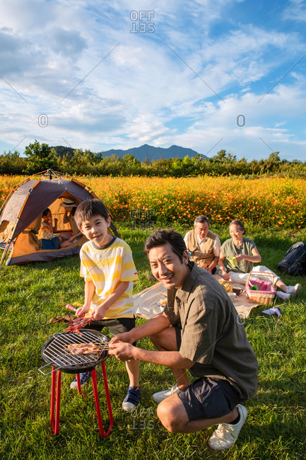 Happy family in a field preparing barbeque for a picnic while camping