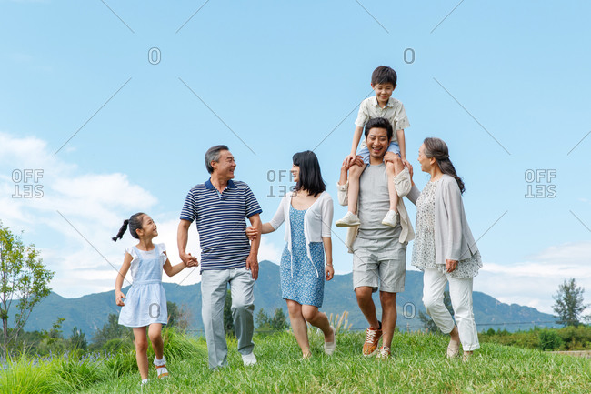 Asian multi-generational family walking together in a grassy field