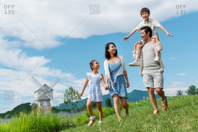 A family of four walking outside together in a field with windmill in background