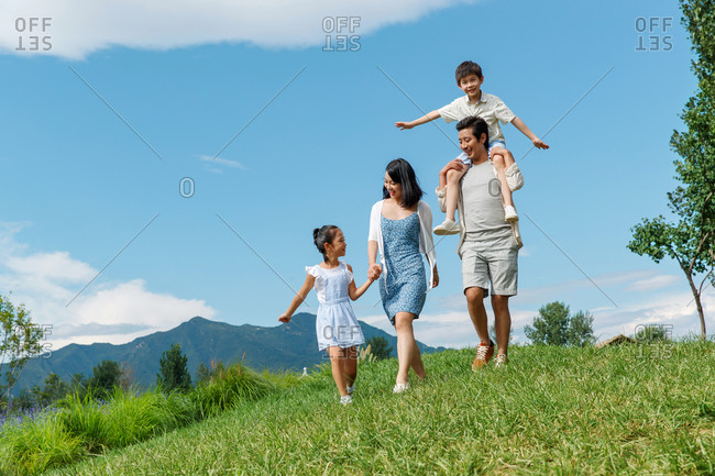 A family of four outside for a walk on a grassy hill in the sunshine