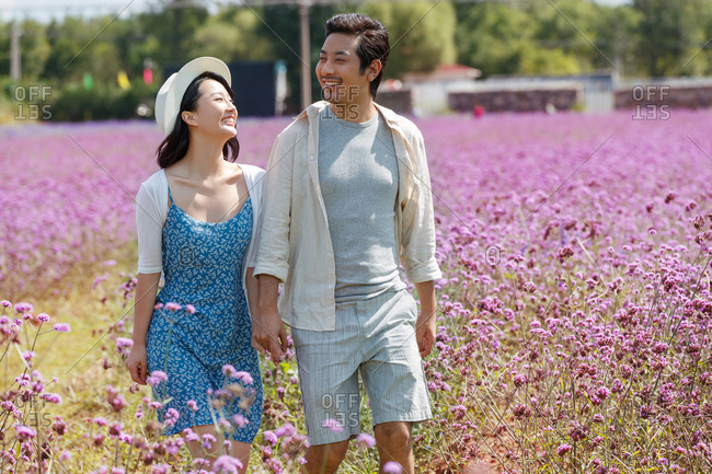 Young Asian couple walking hand in hand in a field of purple flowers