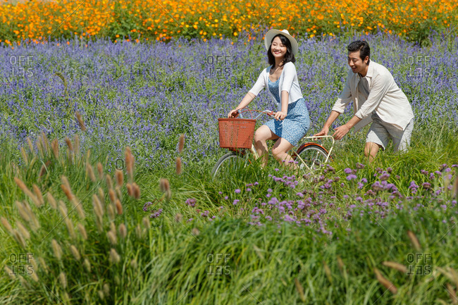 Young couple riding bicycles in a rural field filled with flowers