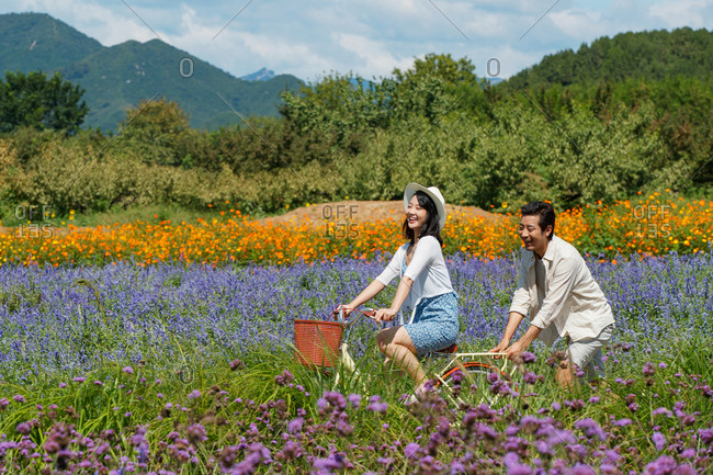 Happy young Asian couple riding bicycles in a rural field filled with flowers