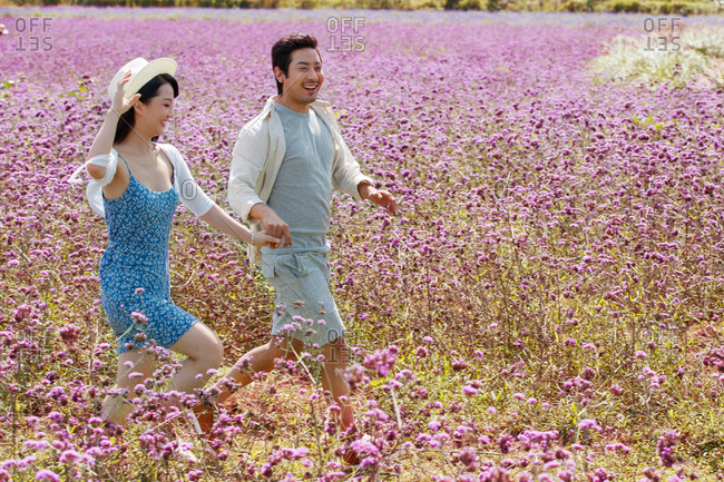 Young couple running hand in hand through a field of purple flowers