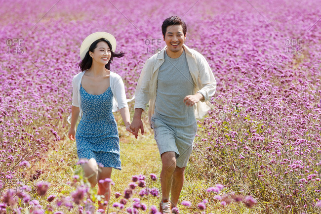 Beautiful young Asian couple running hand in hand in a filed filled with purple flowers