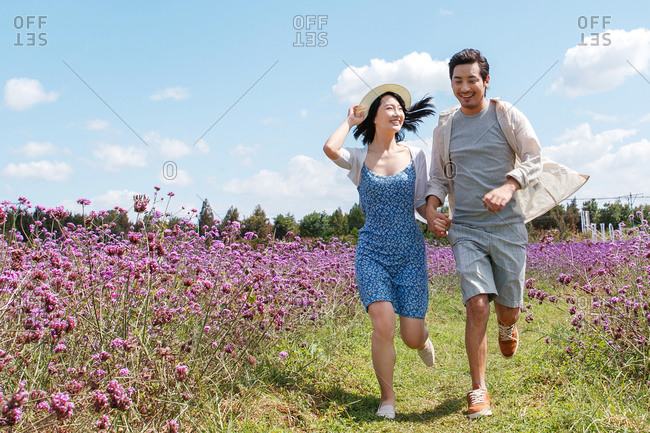 A young Asian couple running hand in hand in a filed filled with purple flowers