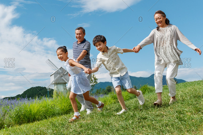 Grandparents walking hand in hand on a grass hillside in front of a windmill with their grandchildren