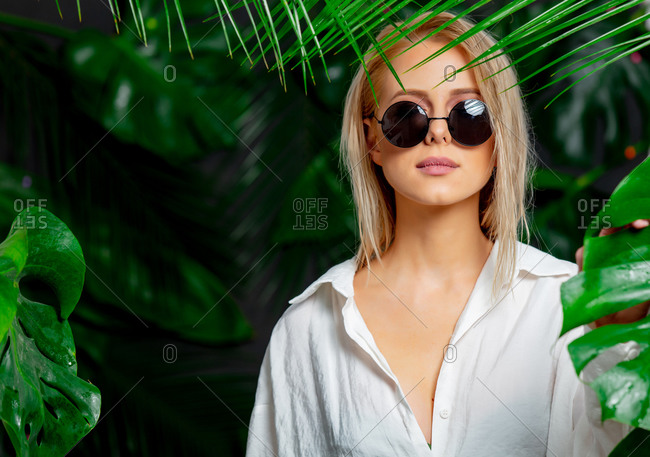 Blonde woman in white shirt and sunglasses around palm leaves