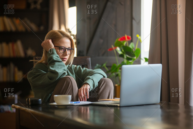 Woman working at home office with laptop. tired