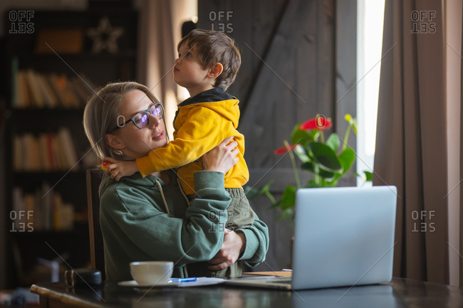 Woman working at home office with laptop and play with a son in same time.