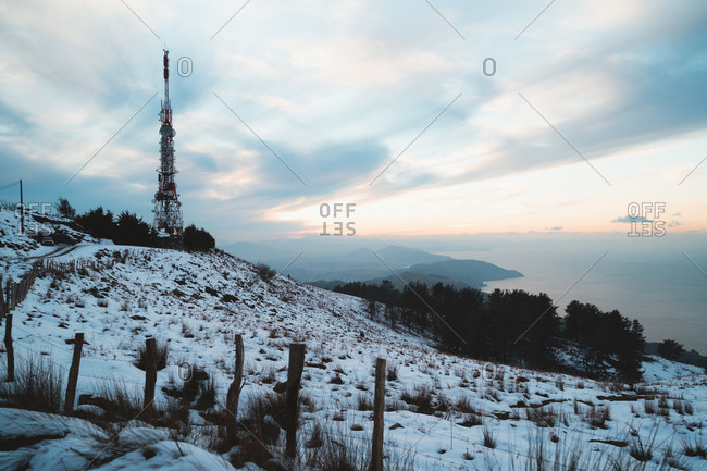 Big radio antenna on top of a snowy hill in the Basque Country during winter