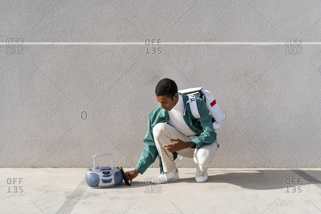 Young man with bag crouching by radio against gray wall