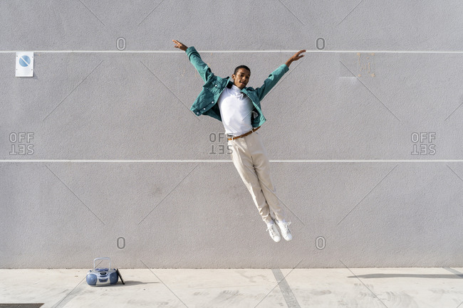 Young man with radio on footpath jumping against gray wall