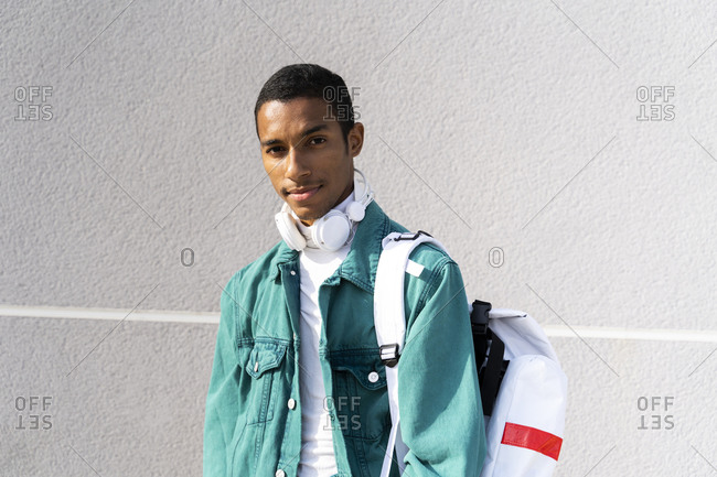 Man with headphones and backpack standing against gray wall