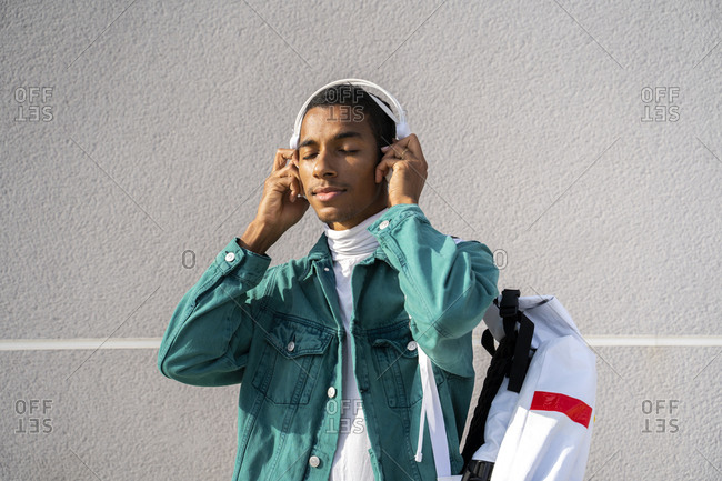 Young man listening music through headphones while standing against gray wall