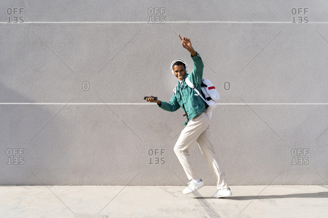 Happy man with headphones and mobile phone dancing while walking against gray wall