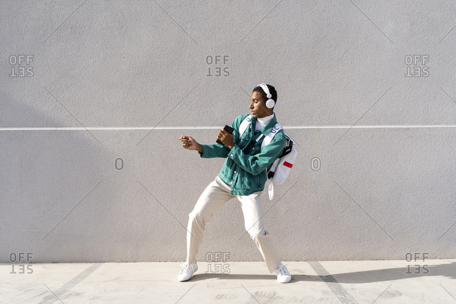 Man wearing headphones listening music while dancing on footpath