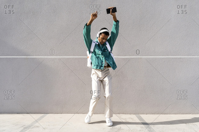 Young man wearing headphones dancing with hand raised while standing on footpath