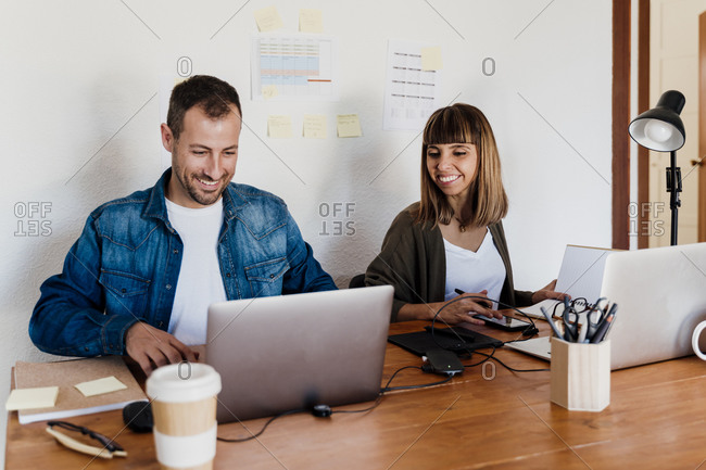 Smiling business couple working together from home in living room