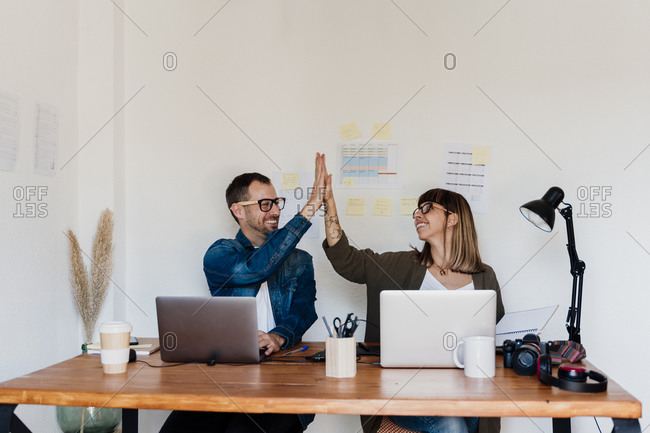 Happy business couple high fiving at home office