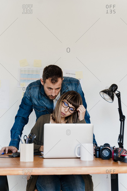 Freelance businesswoman working on laptop while male coworker looking at home office