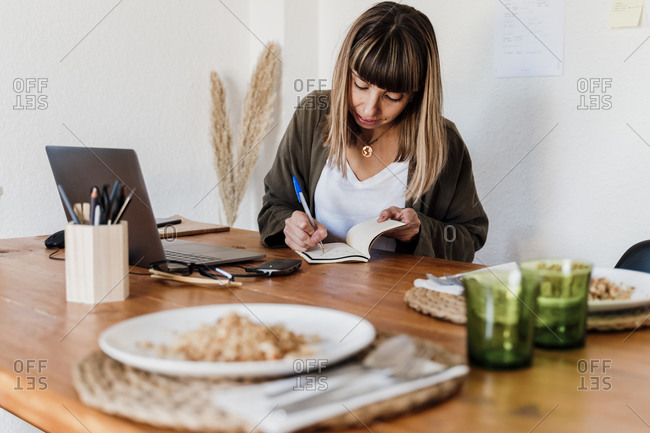 Female professional with food plate on table writing on notepad in home office