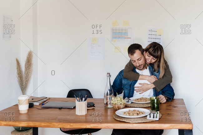 Smiling female professional with arm around embracing male coworker while having food at home office